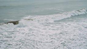 Las ondas grandes suben y se rompen durante una tormenta en un día nublado en la cámara lenta almacen de video
