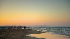 Las ondas ligeras y la gente recolectan después de nadar delante de la puesta del sol en la playa de Malvarros Valencia, España almacen de video