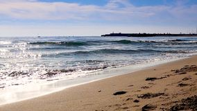 Las ondas mediterráneas de la playa en la playa en el tiempo eavning, luz del sol reflejan en superficie del agua Fuengirola, Esp metrajes