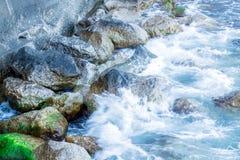 Las ondas que hacen espuma están quebradas contra piedras Imagen de archivo