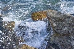 Las ondas que se rompen en la orilla con el mar hacen espuma Foto de archivo