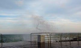 Las ondas que se rompen en un amarre, formando un espray Las ondas rompen el terraplén del mar en tormenta imagenes de archivo