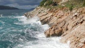 Las ondas que se rompen en una playa pedregosa, formando un aerosol cantidad El salpicar agita en las rocas del mar Fotos de archivo
