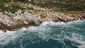 Las ondas que se rompen en una playa pedregosa, formando un aerosol cantidad El salpicar agita en las rocas del mar Imagen de archivo