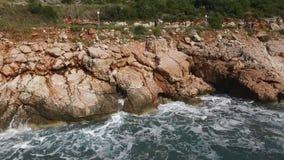 Las ondas que se rompen en una playa pedregosa, formando un aerosol cantidad El salpicar agita en las rocas del mar Imagenes de archivo