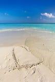 Las ondas quitan un corazón dibujado en la arena de una playa tropical Fotos de archivo