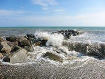 Las ondas se estrellan con un espray de rocas Imagenes de archivo