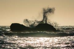 Las ondas se estrellan contra las rocas en la puesta del sol en la playa de Rialto, Washington, los E.E.U.U. Fotografía de archivo