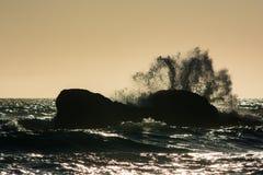 Las ondas se estrellan contra las rocas en la puesta del sol en la playa de Rialto, Washington, los E.E.U.U. Foto de archivo