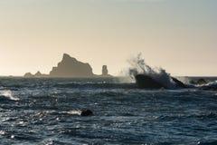 Las ondas se estrellan contra rocas en la playa Washington, los E.E.U.U. de Rialto de la puesta del sol Foto de archivo libre de regalías