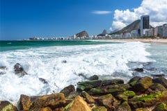 Las ondas se estrellan contra una orilla rocosa en Copacabana Imagen de archivo