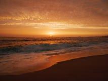 Las ondas se estrellan en la playa arenosa en la puesta del sol con el cielo anaranjado vivo foto de archivo