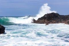 Las ondas se estrellan sobre rocas volcánicas Fotografía de archivo libre de regalías