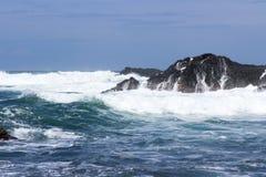 Las ondas se estrellan sobre rocas volcánicas Imágenes de archivo libres de regalías