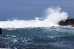 Las ondas se estrellan sobre rocas volcánicas Imagen de archivo