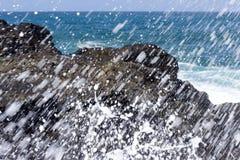 Las ondas se estrellan sobre rocas volcánicas Imagen de archivo libre de regalías