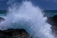 Las ondas se rompen en rocas volcánicas Imagen de archivo libre de regalías