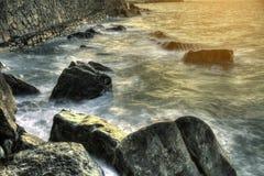 Las ondas sobre rocas en la puesta del sol en el Golfo de Biscaya varan en España Imágenes de archivo libres de regalías