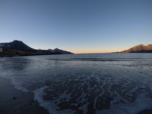 Las ondas tranquilas hermosas del azul que golpean la playa arenosa congelada blanca en último otoño en el Círculo Polar Ártico c Foto de archivo libre de regalías