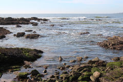 Las ondas van a estrellarse en rocas en una playa en Bretaña (Francia) Imágenes de archivo libres de regalías