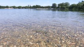 Las orillas del lago con grava en la parte inferior y las pequeñas ondas metrajes