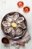 Las ostras abiertas con la salsa y el vino picantes subieron Imagenes de archivo