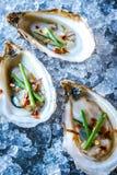 Las ostras de Beau Soleil remataron con las cebolletas y las escamas de pimienta roja imagen de archivo libre de regalías