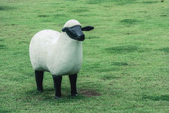Las ovejas blancas esculpen la situación en hierba verde en el parque público Fotos de archivo