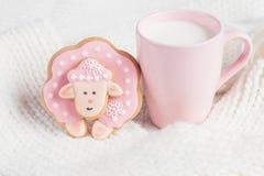 Las ovejas rosadas del pan de jengibre con la taza de leche en blanco hicieron punto backgro Foto de archivo