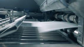Las páginas de papel reveladas están consiguiendo lanzadas sobre la correa del transportador metrajes