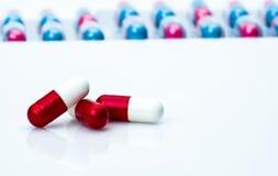 las píldoras antibióticos Rojo-blancas de la cápsula en píldoras embalan el fondo borroso con el espacio de la copia para el text Imagen de archivo libre de regalías