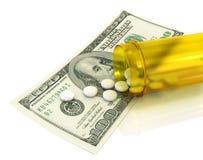 Las píldoras blancas vertieron de un tarro que 100 billetes de dólar Foto de archivo