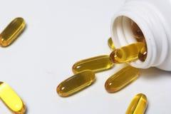 Las píldoras del color amarillo se vierten en una superficie blanca de los tarros plásticos Foto de archivo
