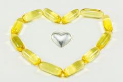 Las píldoras en forma del corazón y corazón de la plata Fotos de archivo libres de regalías