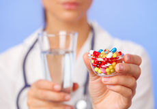 Las píldoras, las tabletas y las drogas apilan en mano del doctor Fotografía de archivo