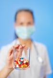 Las píldoras, las tablillas y las drogas apilan en la mano del doctor foto de archivo libre de regalías