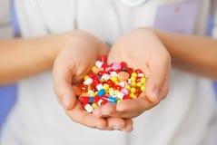 Las píldoras, las tablillas y las drogas apilan en la mano del doctor Fotografía de archivo libre de regalías