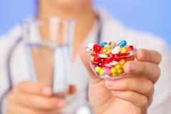 Las píldoras, las tablillas y las drogas apilan en mano del doctor Foto de archivo