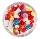 Las píldoras, las tablillas y las drogas apilan en vidrio imagenes de archivo
