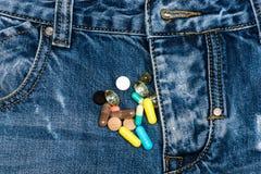 Las píldoras o las tabletas de la medicina dispersaron en vaqueros cerca relampagan, fondo del dril de algodón Concepto genitouri foto de archivo