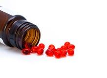 Las píldoras rojas se derramaron cerca de una botella de píldora Imagenes de archivo