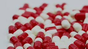 Las píldoras rojas y blancas de la cápsula de los antibióticos resbalan y moviéndose de la derecha hacia la izquierda Concepto de almacen de video
