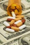 Las píldoras se derramaron sobre el dinero Foto de archivo libre de regalías