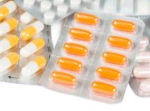 Las píldoras y las cápsulas de la medicina embalaron en las ampollas aisladas Imagenes de archivo