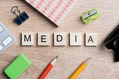 Las palabras conceptuales de los medios de comunicación deletrearon con los cubos de madera en el escritorio imagen de archivo libre de regalías