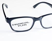 Las palabras financieras del plan consideran a través la lente de los vidrios, concepto del negocio Foto de archivo libre de regalías