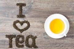 Las palabras I aman el té hecho de hojas de té verdes con una taza de té Foto de archivo libre de regalías