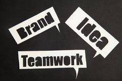Las palabras idea, trabajo en equipo y marca en burbujas del discurso Imagen de archivo