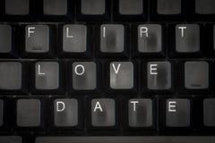 Las palabras ligan, quieren, fechan en un teclado negro Imagen de archivo
