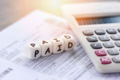 Las palabras pagadas y el papel de la cuenta de la factura de la calculadora por tiempo pagaron el pago en las finanzas del negoc foto de archivo libre de regalías